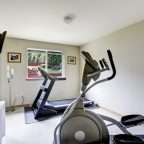 Bright gym room with exercise equipments and tv